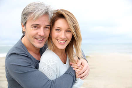 Foto de Cheerful mature couple embracing by the beach - Imagen libre de derechos