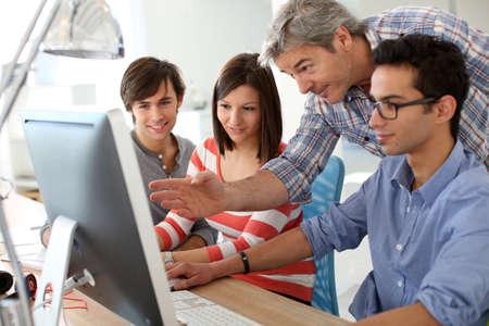 Foto de Teacher with students working on desktop  - Imagen libre de derechos