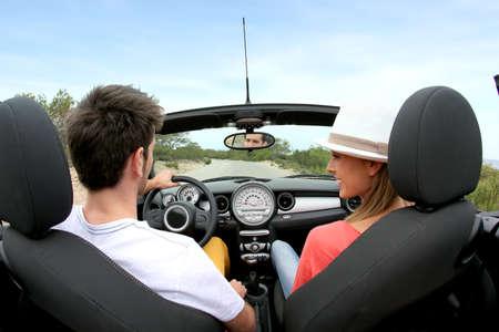 Photo pour Young couple driving convertible car - image libre de droit