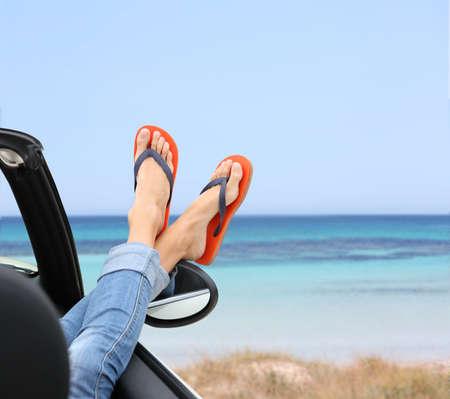 Photo pour Closeup of woman's feet by convertible car window - image libre de droit