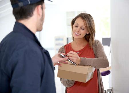 Photo pour Woman sigining electronic receipt of delivered package  - image libre de droit
