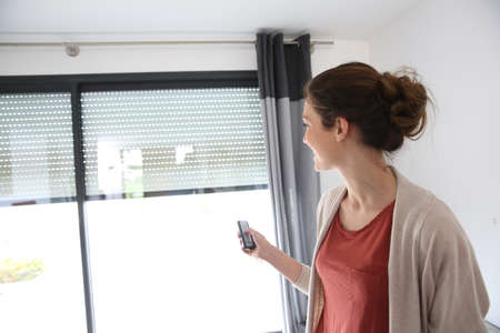 Photo pour Woman using remote control to open electric shutter - image libre de droit