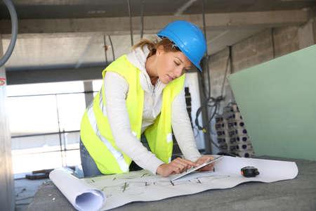 Photo pour Woman architect on building site using tablet - image libre de droit