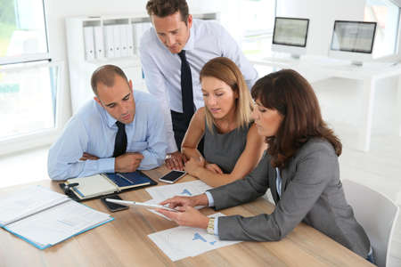 Group of business people meeting around table wih tablet