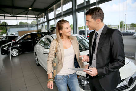 Photo pour Car dealer showing vehicle to woman - image libre de droit