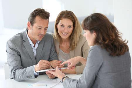 Photo pour Couple signing loan grant on digital tablet - image libre de droit