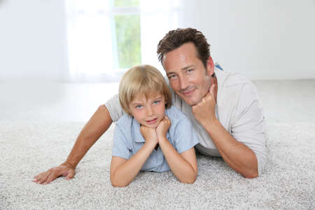 Father and son laying on carpet at home