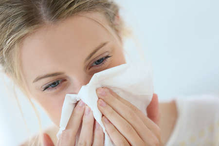 Foto de Young woman with cold blowing her runny nose - Imagen libre de derechos