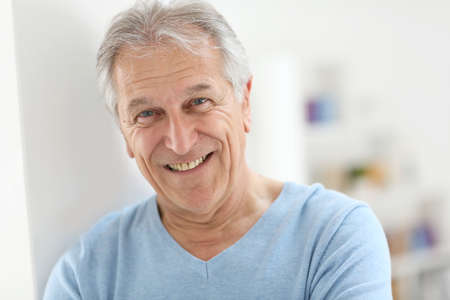 Foto de Portrait of smiling senior man with blue shirt - Imagen libre de derechos