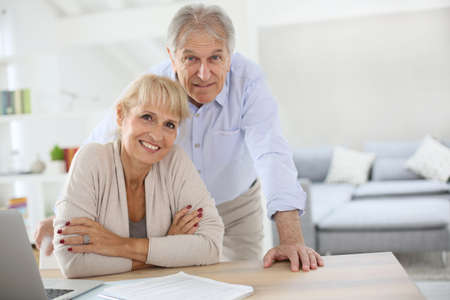 Photo for Senior couple at home filling pension paper - Royalty Free Image
