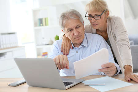 Photo for Senior couple doing the income tax declaration online - Royalty Free Image