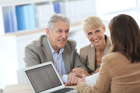 Photo pour Senior couple meeting financial adviser in office - image libre de droit