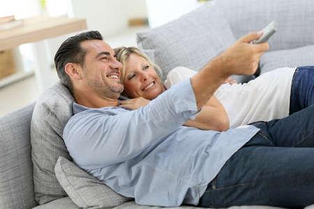 Photo pour Middle-aged couple in sofa watching tv - image libre de droit