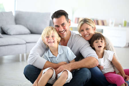 Foto de Portrait of happy family sitting on floor - Imagen libre de derechos