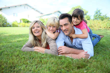 Photo for Family of four laying on grass in front of house - Royalty Free Image