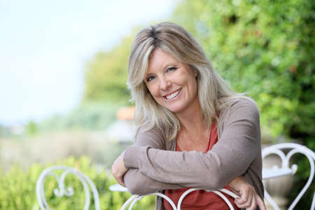 Portrait of smiling mature blond woman in garden