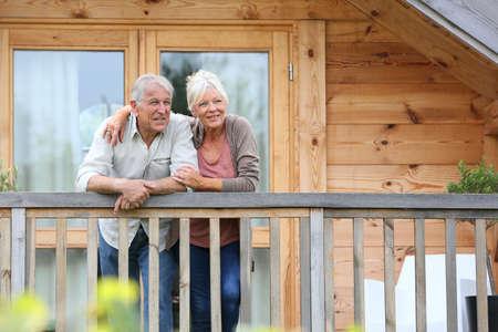 Foto de Senior couple standing oustide log cabin in countryside - Imagen libre de derechos