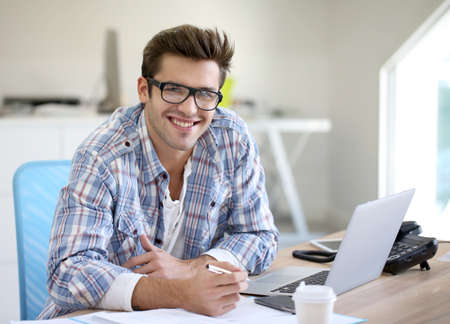 Photo for Young man in office working on laptop computer - Royalty Free Image