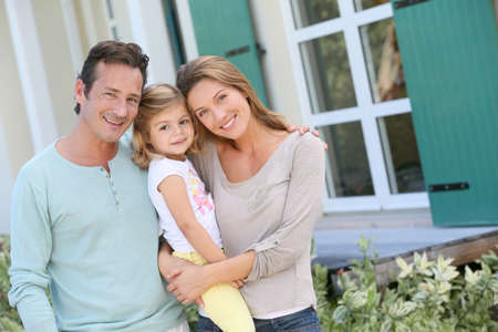 Photo for Portrait of happy family standing in front of house - Royalty Free Image