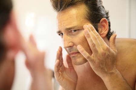 Foto de Middle-aged man in bathroom applying facial lotion - Imagen libre de derechos