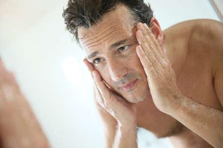 Foto de Handsome man rinsing face after shaving - Imagen libre de derechos