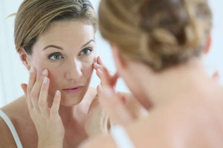 Foto de Middle-aged woman applying anti-aging cream - Imagen libre de derechos