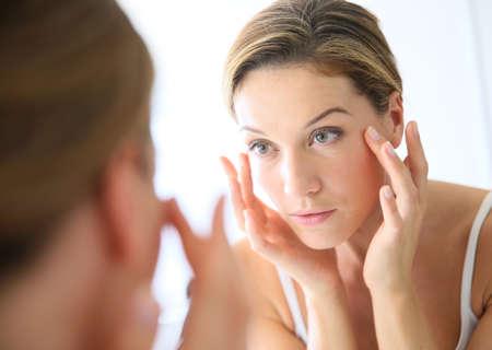 Photo pour Middle-aged woman applying anti-aging cream - image libre de droit