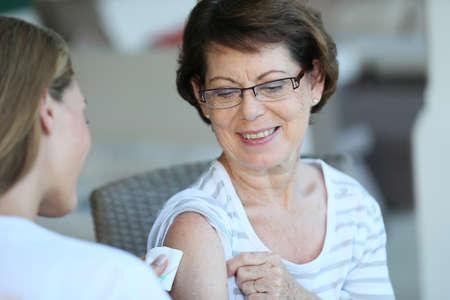 Foto de Senior woman receiving flu vaccine - Imagen libre de derechos