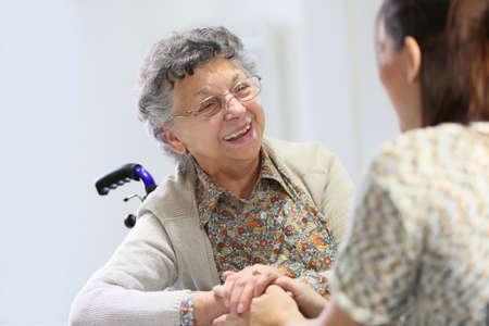 Foto de Elderly woman sharing good time with home carer - Imagen libre de derechos