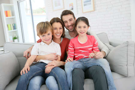 Foto de Cheerful family at home sitting in sofa - Imagen libre de derechos