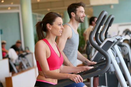 Couple doing cardio training program in fitness center