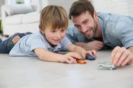 Foto de Daddy with little boy playing with toy cars - Imagen libre de derechos