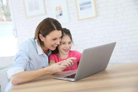 Foto de Mother and daughter playing on laptop computer - Imagen libre de derechos