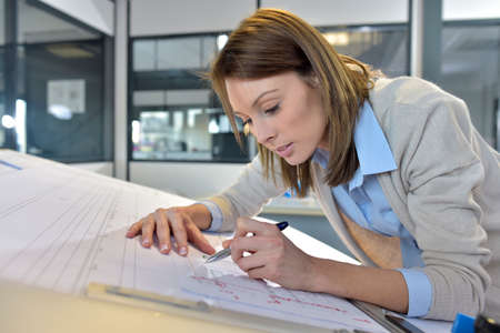 Photo pour Woman engineer working on blueprint in office - image libre de droit