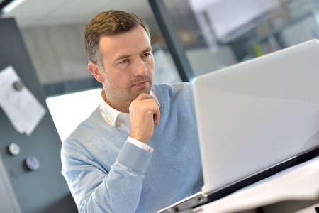 Photo for Industrial manager in office working on laptop - Royalty Free Image
