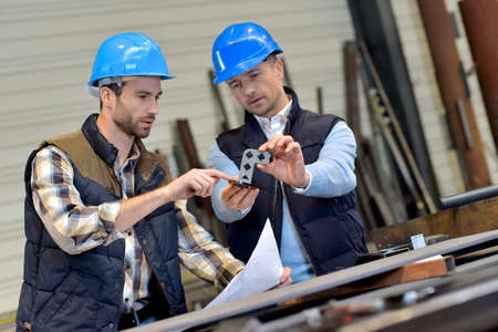 Photo pour Engineer with mechanical worker checking on production - image libre de droit