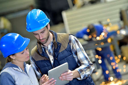 Photo for Engineers in steel factory working on digital tablet - Royalty Free Image