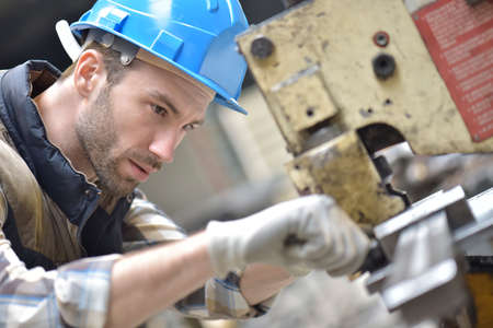 Photo for Industrial worker working on machine in factory - Royalty Free Image