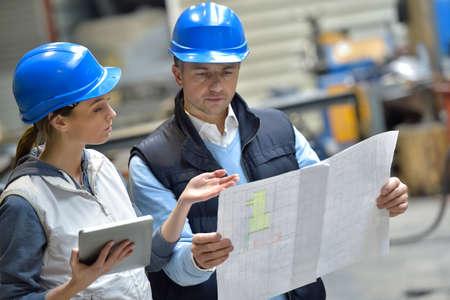 Foto de Engineers in mechanical factory reading instructions - Imagen libre de derechos