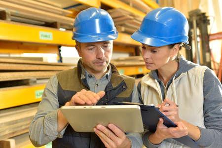 Foto de Worker with overseer controling stock in warehouse - Imagen libre de derechos