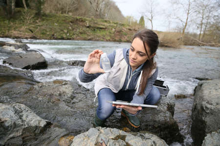 Photo pour Student in biology taking sample of natural water - image libre de droit