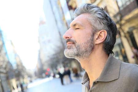Photo pour Portrait of serene mature man in town - image libre de droit