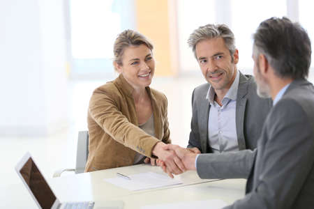 Photo pour Couple in bank office shaking hand to financial adviser - image libre de droit