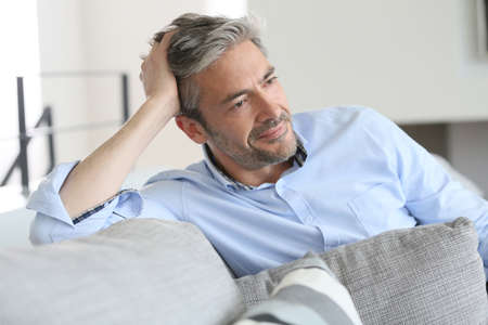 Photo for Smiling handsome 45-year-old man relaxing at home - Royalty Free Image