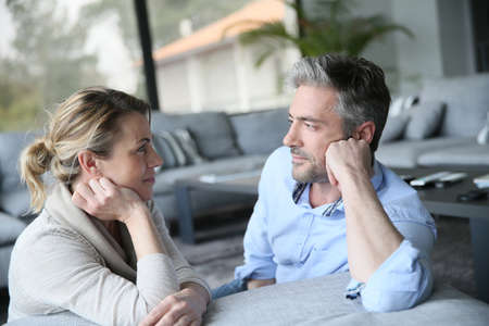 Foto de Mature couple talking to each other in sofa - Imagen libre de derechos