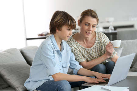 Photo for Mother looking after son doing homework on laptop - Royalty Free Image