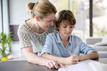 Foto de Mother helping kid with homework - Imagen libre de derechos
