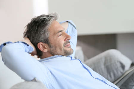 Photo for Middle-aged man having a restful moment relaxing in sofa - Royalty Free Image