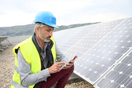 Foto de Mature engineer on building roof checking solar panels - Imagen libre de derechos