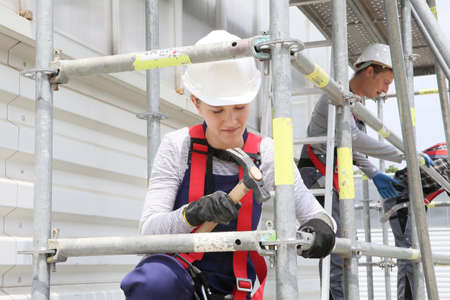 Photo pour Young woman in professional training working on scaffolding - image libre de droit